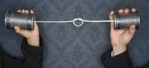 Dosentelefon mit Knoten. Zwei Hände halten jeweils eine Dose, die durch einen Faden verbunden sind.