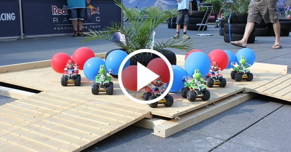 Mario Karts mit Luftballons stehen auf Holz-Plattform