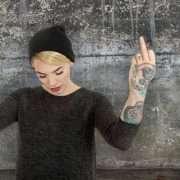 Blondes Mädchen mit Mütze und Tattoo zeigt beide Stinkefinger