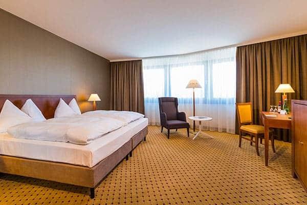 Standard Zimmer beim Ramada Graz mit schönem Bett und Teppichboden