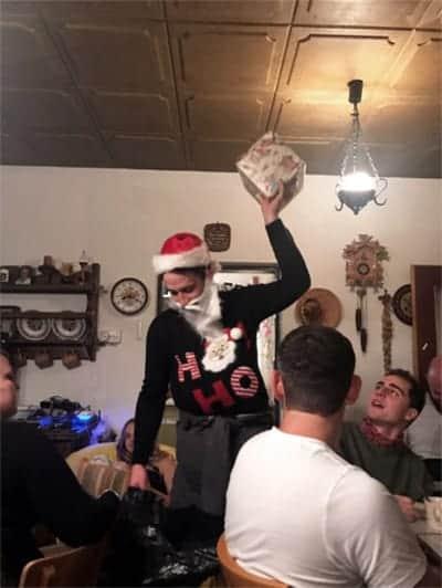 Mann ist als Weihnachtsmann verkleidet und hält ein Geschenk