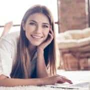 Frau liegt am Teppich und lernt selbstständig dank der Digitalisierung der Weiterbildung
