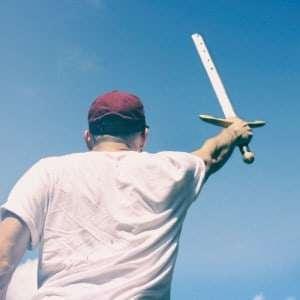 Mann hält beim Teambuilding Spiel das Schwert Excalibur hoch
